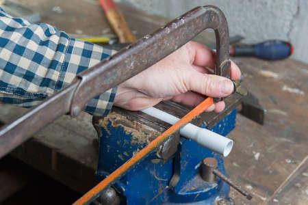 serrucho: hombre cortar tuber�a de PVC con un serrucho
