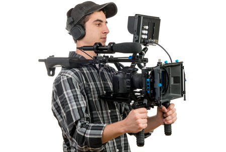 young cameraman with movie camera on the white background Stock Photo