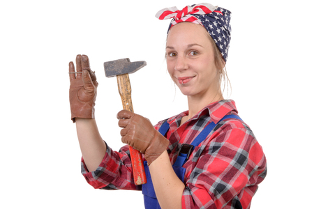 young woman handyman drive a nail with a hammer photo