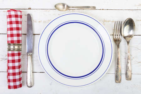 silver cutlery: plate with silver cutlery on an old white table Stock Photo