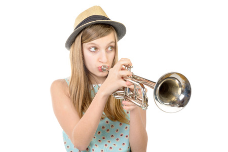 teenager with a hat plays the trumpet Foto de archivo