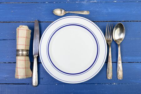 silver cutlery: plate with silver cutlery on an old blue table