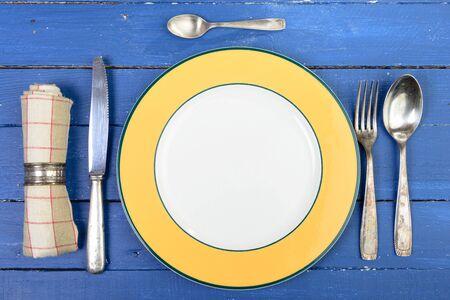 古い青いテーブルの上の銀のカトラリーとプレート