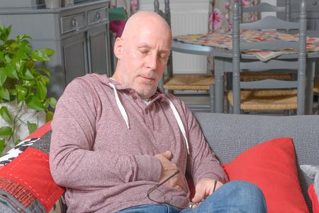 een man van middelbare leeftijd heeft een maagpijn Stockfoto
