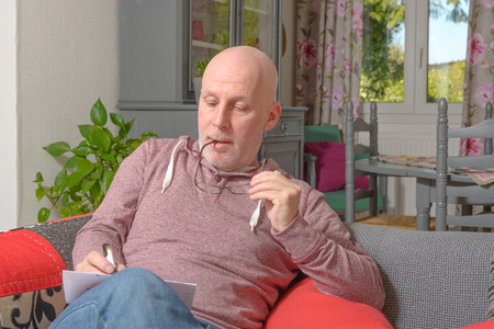 a middle-aged man writing a letter on the sofa