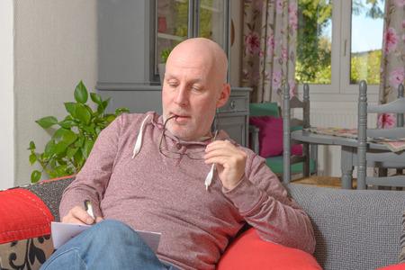 papier a lettre: un homme d'�ge moyen � �crire une lettre sur le canap�