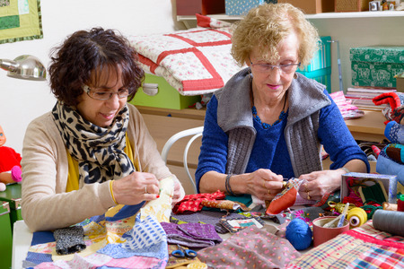 twee vrouwen werken aan hun patchwork in de werkplaats Stockfoto