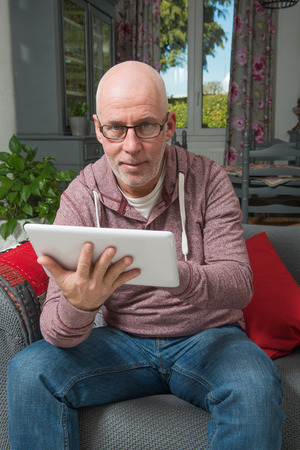 adultery: a senior man with a digital tablet on the sofa Stock Photo