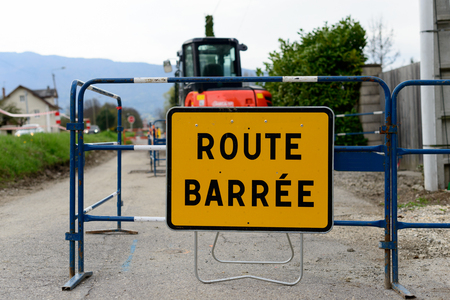 road closed: A yellow road sign road closed with work vehicle