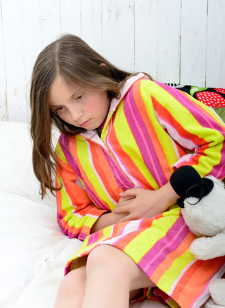 a little girl in her bed has a stomach ache