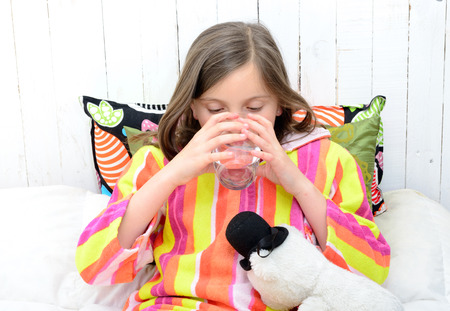 glass bed: a sick girl drinking a glass of water in her bed Stock Photo