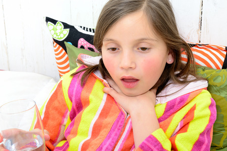 tonsillitis: a little girl has a sore throat in her bed Stock Photo