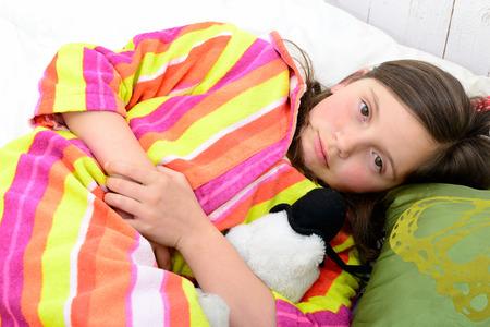 그녀의 침대에있는 어린 소녀는 복통이있다.