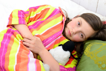 a little girl in her bed has a stomachache