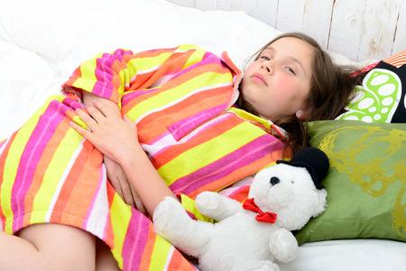 그녀의 침대에있는 어린 소녀는 위가 아프다.