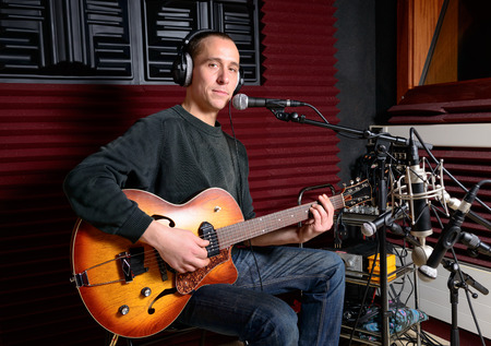 a singer and his guitar in a recording studio