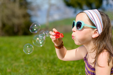 making: a little girl making soap bubbles in nature