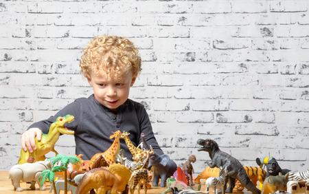 kinderen: een klein kind speelt met speelgoed dieren en dinosaurus Stockfoto