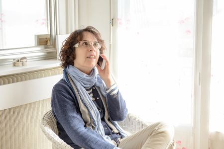 a mature woman with a mobile phone sitting in chair photo