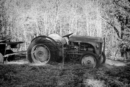 old tractor: an old tractor abandoned in a field in black and white