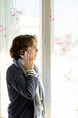 a mature woman with a white mobile phone photo