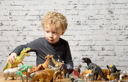 een klein kind speelt met speelgoed dieren en dinosaurus Stockfoto
