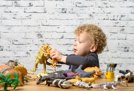 plaything: a little child plays with toys animals and dinosaur Stock Photo