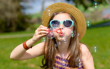 kid portrait: a little girl making soap bubbles in nature