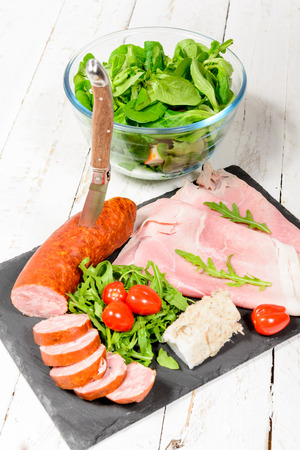 charcuter�a: plato de embutidos con ensalada y tomates Foto de archivo