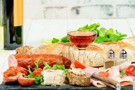 charcutería: plato de embutidos con vino, pan y tomates Foto de archivo