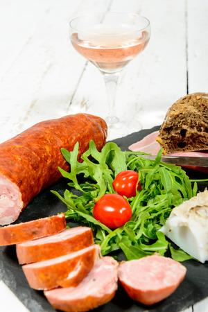 charcuter�a: plato de embutidos con vino, pan y tomates Foto de archivo