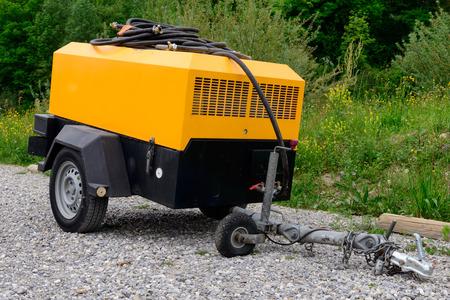 een gele compressor site op gravel Stockfoto