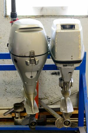 outboard: two outboard motors in a repair shop