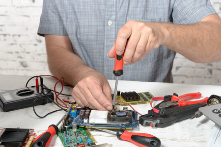a technician repairing a computer with different tools 版權商用圖片