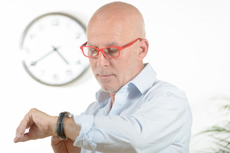 a man with red glasses looks at his watch photo