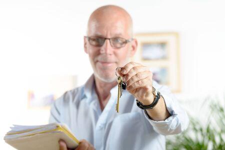een makelaar geeft de sleutels van het huis