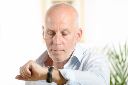 a man  looks at his watch in his office photo
