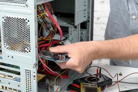 a technician repairing a computer with different tools Standard-Bild
