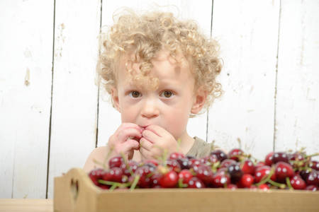 eats: a small blond boy eating cherries