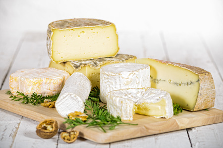 different french cheeses on old white table