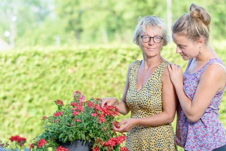 caring for: a mother and daughter caring for flowers in their garden