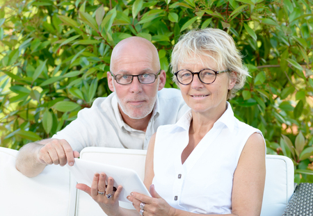 a couple of seniors looking at digital tablet outside