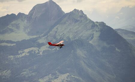 cessna: a small red airplane flying over the French Alps
