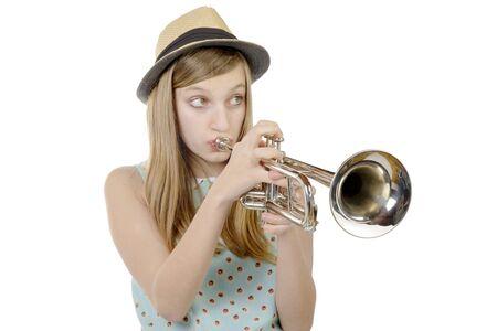 trompeta: una linda chica toca la trompeta en el fondo blanco Foto de archivo