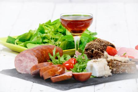 charcutería: plato de embutidos con pan vino y ensalada