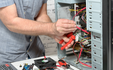 a technician repairing a computer with different tools Stock Photo