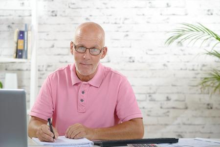 분홍색 폴로 셔츠와 사업가 그의 사무실에서 작동