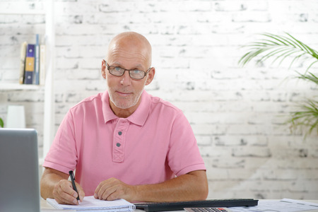a businessman with a pink polo shirt works in his office 版權商用圖片
