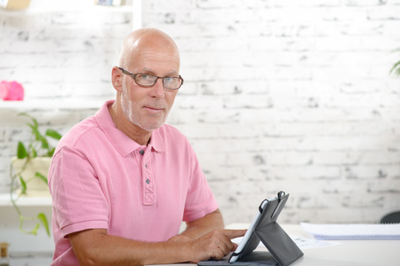 a businessman with a pink polo shirt look a digital tablet