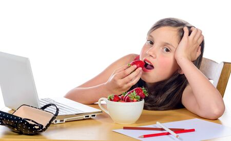 eats: a pretty little girl eats strawberries on white background Stock Photo